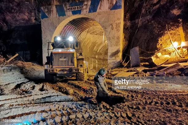 In this picture taken on February 8, 2021 an army personnel interacts with a stray dog called Blackie near the entrance of Tapovan tunnel, where...