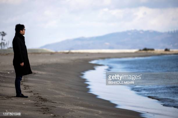 In this picture taken on February 8 Nayuta Ganbe, who survived Japan's devastating 2011 tsunami by taking shelter at his school, poses as he looks at...