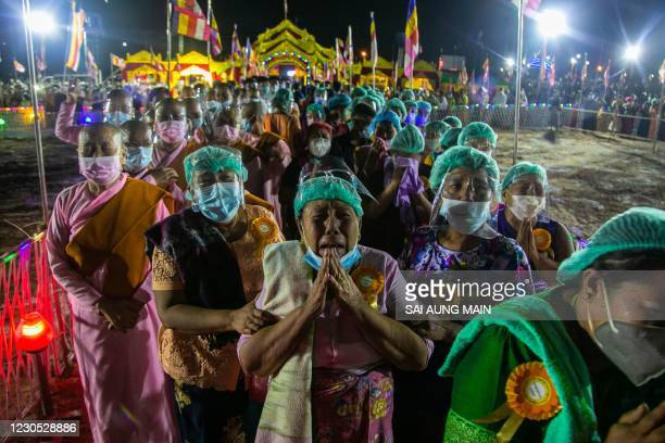 In this picture taken on January 10 devotees cry as they gather to pay their respectss during the cremation of monk Wai Bu La in Thanlyin, Yangon,...