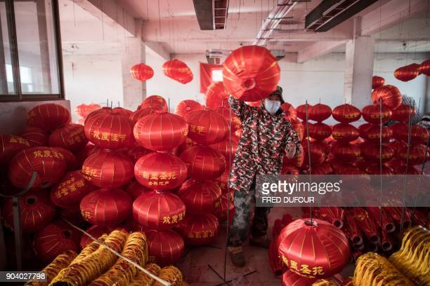 In this picture taken on January 11 2018 a Chinese worker folds red lanterns at a factory for the upcoming Lunar New Year celebrations on February 15...