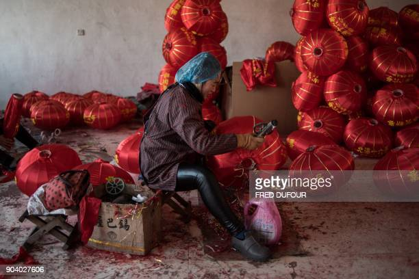 In this picture taken on January 11 2018 a Chinese worker makes red lanterns ahead of the upcoming Lunar New Year celebrations on February 15 at a...