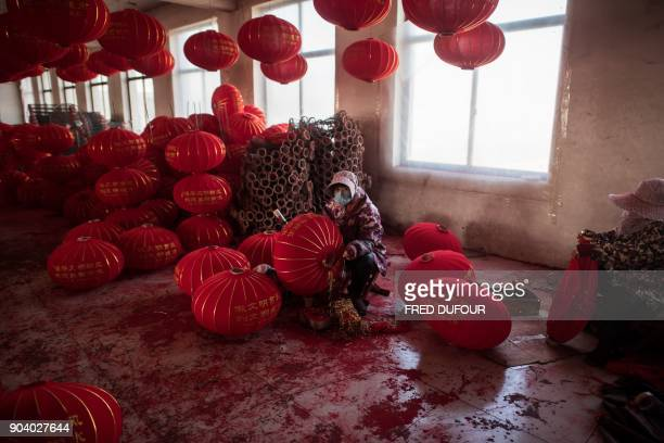 TOPSHOT In this picture taken on January 11 2018 a Chinese worker makes red lanterns ahead of the upcoming Lunar New Year celebrations on February 15...