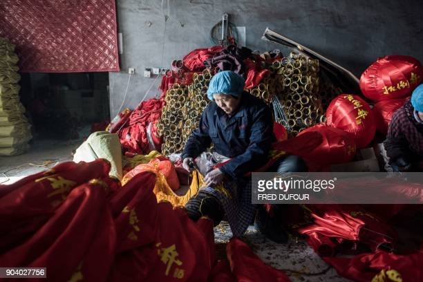 In this picture taken on January 11 2018 a Chinese worker makes red lanterns for the upcoming Lunar New Year celebrations on February 15 at a factory...