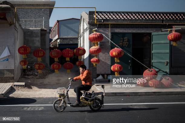 In this picture taken on January 11 2018 a young man rides his scooter past red lanterns ahead of the upcoming Lunar New Year celebrations on...