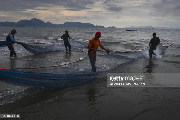 In this picture taken on January 12 2018 Acehnese fishermen hold a net to fish on the beach of Banda Aceh According to the Indonesian Central...