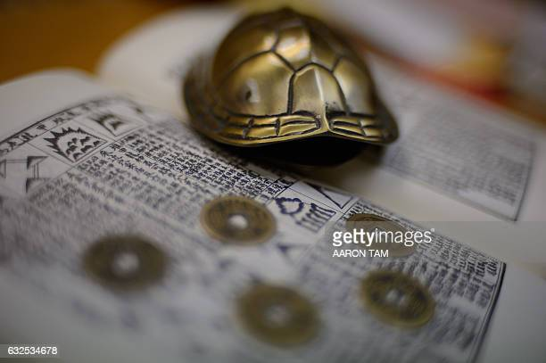 In this picture taken on January 14 a metal turtle shell and Chinese coins used for predictions are seen in the office of Hong Kong feng shui master...