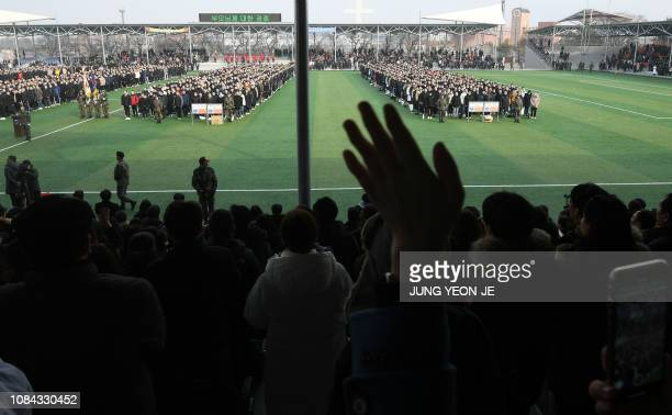 TOPSHOT In this picture taken on January 14 family members of South Korean military conscripts wave farewell to their boys during an induction...