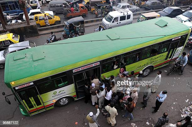 In this picture taken on January 14 Pakistani commuters board a compressed natural gas -powered Green Bus, newly introduced to Karachi, on the city's...