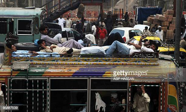 In this picture taken on January 14 Pakistani commuters lie atop a bus driving down Karachi's busiest street, Mohammad Ali Jinnah Road. AFP PHOTO/...