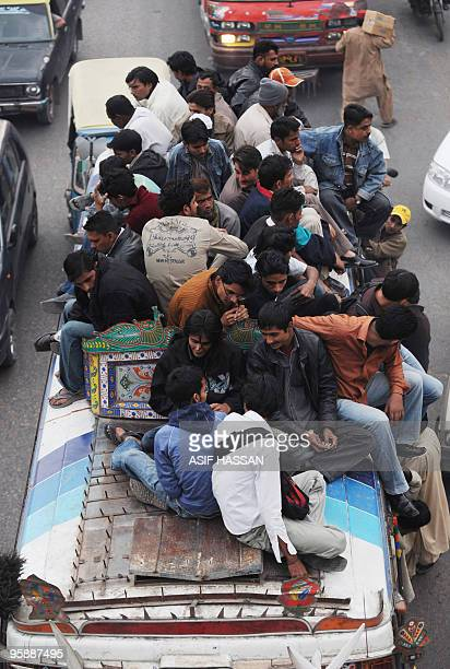 In this picture taken on January 14 Pakistani commuters sit atop a bus driving down Karachi's busiest street, Mohammad Ali Jinnah Road. AFP PHOTO/...
