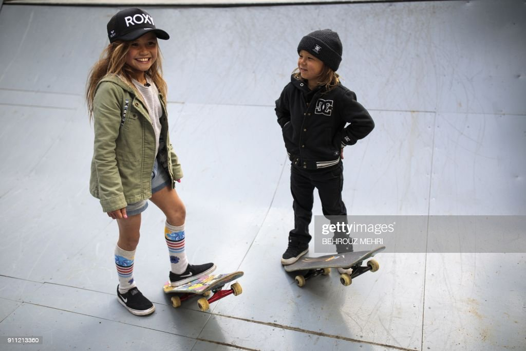 In this picture taken on January 14, 2018, Sky Brown (L) and her brother Ocean (R) pose with their skateboards on a half-pipe at a park in Kijo town, Miyazaki prefecture. Nine-year-old Sky Brown has set her sights on Tokyo 2020, when the hipster sport makes its Olympic bow, along with surfing, karate and sports climbing. / AFP PHOTO / Behrouz MEHRI / TO