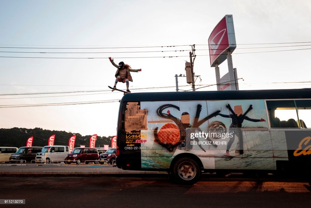 In this picture taken on January 14, 2018, Sky Brown does a roll in as she drops from the top of a bus with her name sprayed on it in Takanabe town, Miyazaki prefecture. Nine-year-old Sky Brown has set her sights on Tokyo 2020, when the hipster sport makes its Olympic bow, along with surfing, karate and sports climbing. / AFP PHOTO / Behrouz MEHRI / TO