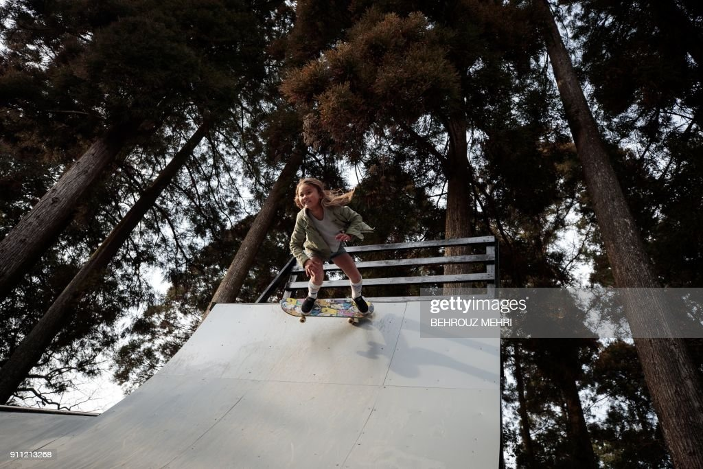 In this picture taken on January 14, 2018, Sky Brown shows her skateboarding skills on the half-pipe at a park in Kijo town, Miyazaki prefecture. Nine-year-old Sky Brown has set her sights on Tokyo 2020, when the hipster sport makes its Olympic bow, along with surfing, karate and sports climbing. / AFP PHOTO / Behrouz MEHRI / TO