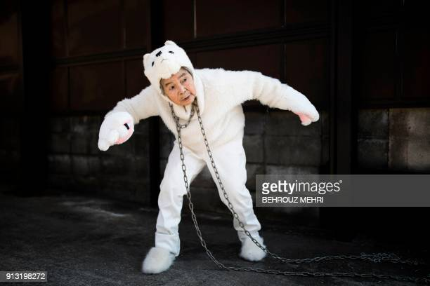 In this picture taken on January 16 Kimiko Nishimoto, dressed in a dog costume, gestures during a self photoshoot outside her house in the western...