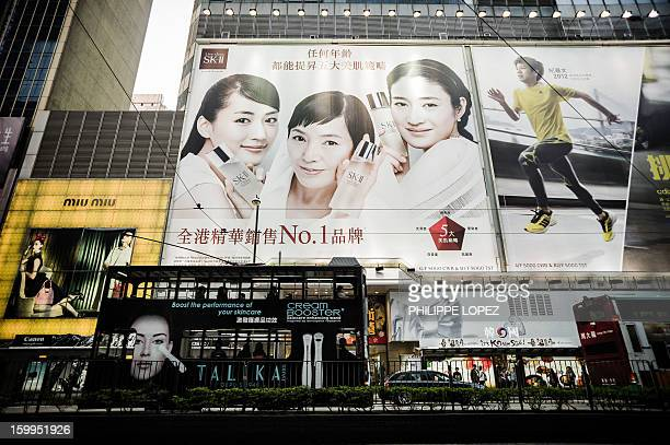 In this picture taken on January 17 2013 a tram drives past billboards in Hong Kong Trundling along slowly against a backdrop of glittering...