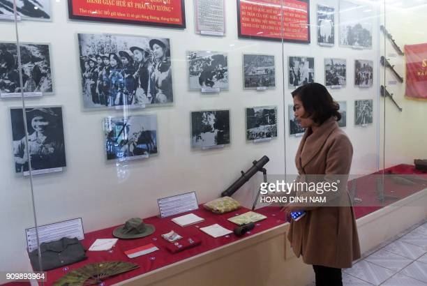 In this picture taken on January 17 a guide speaks next to a display of photographs and items related to the 1968 'Tet Offensive' at the...