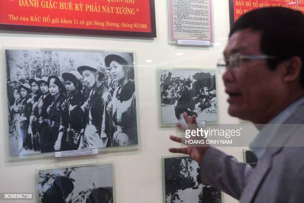 In this picture taken on January 17 Cao Huy Hung director of the Revolutionary Museum of Hue gestures at a photograph showing the Perfurme River...