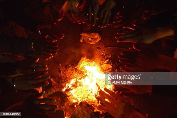 TOPSHOT In this picture taken on January 17 Indian people warm up around a fire during a cold evening in Jalandhar