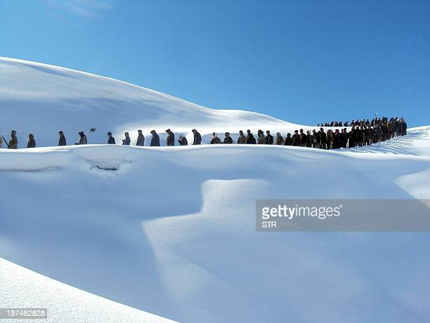 In this picture taken on January 18, 2012 Afghan rescue workers walk in a line into a snowbound village in the mountainous northeastern Afghanistan...