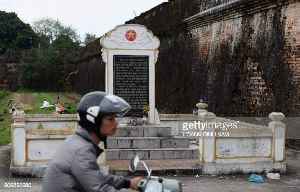In this picture taken on January 18 a motorcyclist rides past a memorial erected next to a gate of the former imperial citadel where fierce fighting...