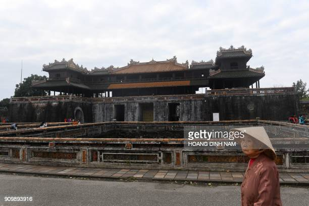 In this picture taken on January 18 an elderly woman walks in front of the former imperial citadel where fierce fighting took place during the 1968...