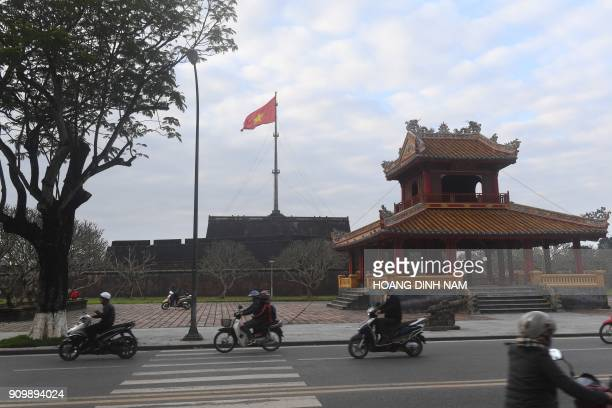 In this picture taken on January 18 motorcyclists ride past the main flag mast of the former imperial citadel where fierce fighting took place during...