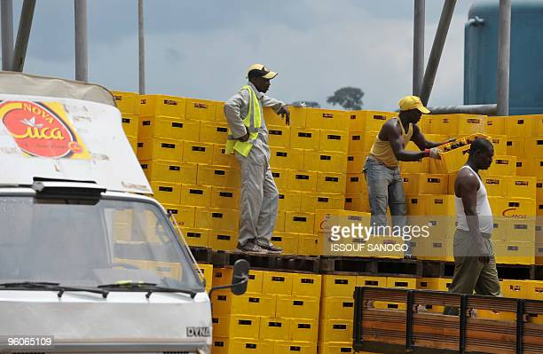 In this picture taken on January 22 2010 workers at the French owned brewery where the popular beer Cuca is produced stack crates at the brewery in...