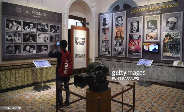 In this picture taken on January 22 a student takes a picture of a display with images of former Indian movie actors at the National Museum of Indian...