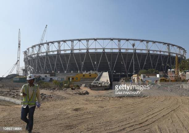 In this picture taken on January 25 An Indian official walks past a construction site of the worlds largest cricket stadium at Motera, some 11 km...