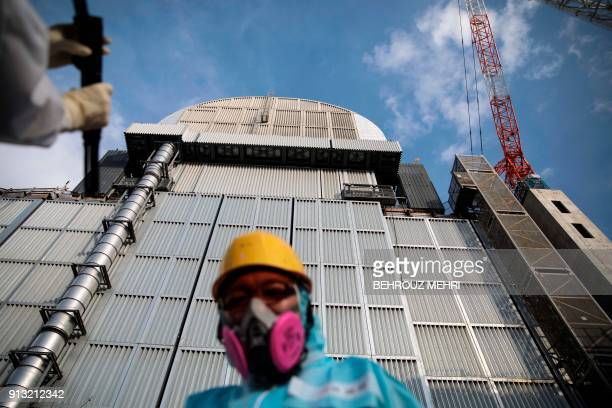 In this picture taken on January 31 2018 an employee of Tokyo Electric Power Company stands in front of the company's reactor number 3 at Fukushima...