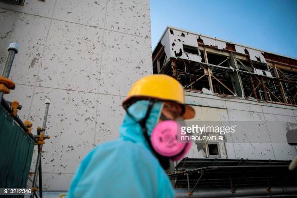 In this picture taken on January 31 2018 an employee of Tokyo Electric Power Company walks past an ice wall at Fukushima Daiichi nuclear power plant...