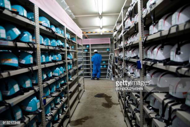 In this picture taken on January 31 2018 an employee of Tokyo Electric Power Company stands next to shelves of safety helmets at Fukushima Daiichi...