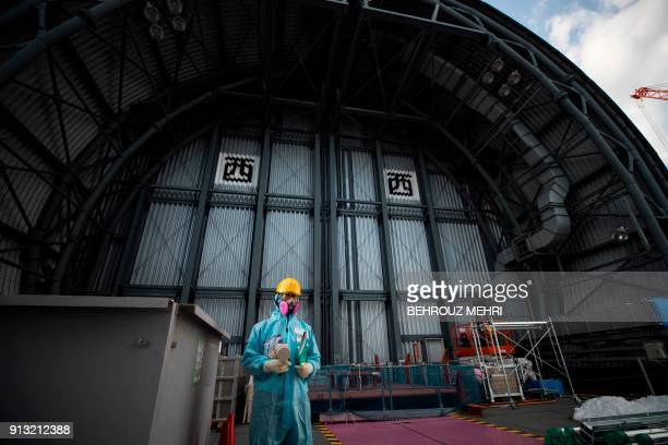 TOPSHOT In this picture taken on January 31 2018 an employee of Tokyo Electric Power Company holds a geiger counter to measure radiation on the top...