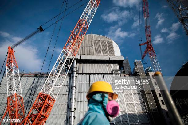 In this picture taken on January 31 2018 an employee of Tokyo Electric Power Company walks past the company's reactor number 3 at Fukushima Daiichi...