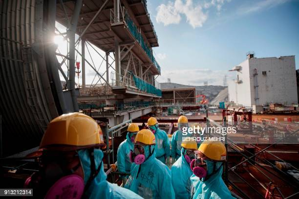 In this picture taken on January 31, 2018 employees of Tokyo Electric Power Company stand in front of the company's reactor number 3 at Fukushima...