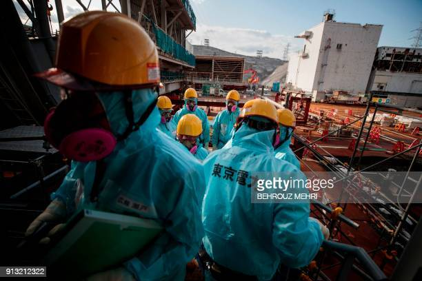 TOPSHOT In this picture taken on January 31 2018 employees of Tokyo Electric Power Company stand in front of the company's reactor number 3 at...