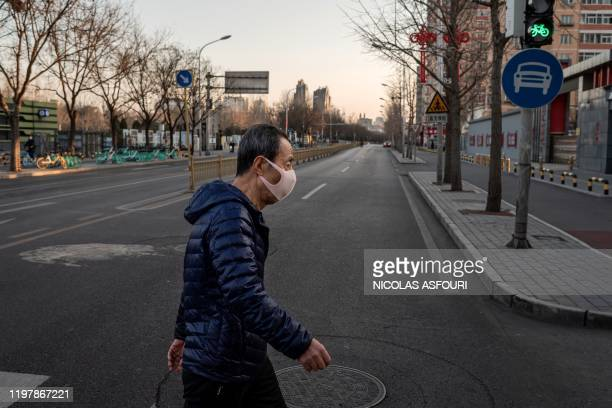 In this picture taken on January 31 a man wearing a protective mask as a preventative measure following a virus outbreak which began in the Chinese...