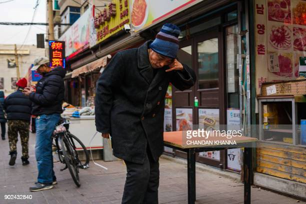In this picture taken on January 7 a man pretends to be talking on a phone at one of China's largest Korea towns in Shenyang in China's northeastern...