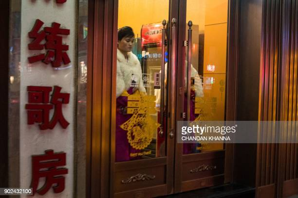 TOPSHOT In this picture taken on January 7 a North Korean worker stands at the entrance of a North Korean restaurant located in one of China's...