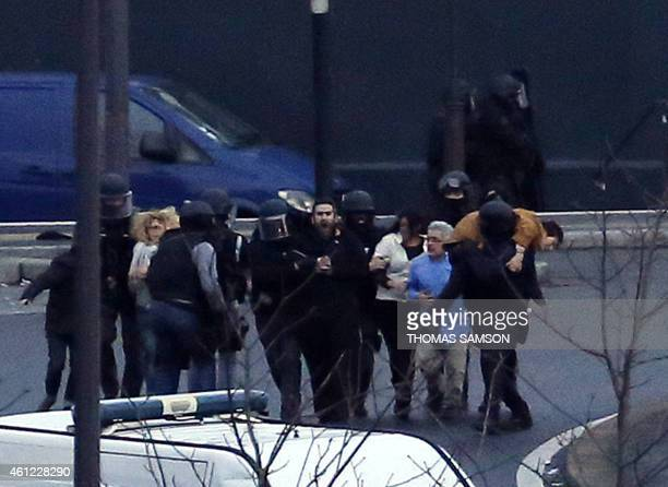 In this picture taken on January 9 2015 members of the French police special forces evacuate the hostages after launching the assault at the Hyper...