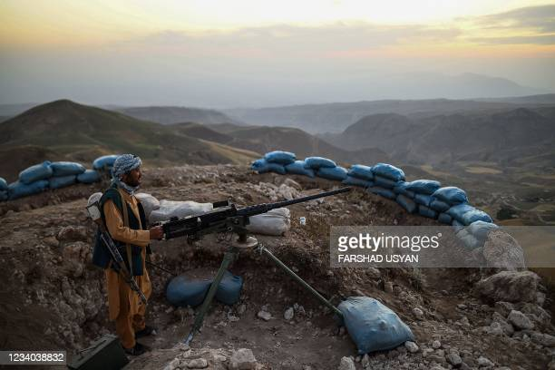 In this picture taken on July 11, 2021 an Afghan militia fighter keeps a watch at an outpost against Taliban insurgents at Charkint district in Balkh...