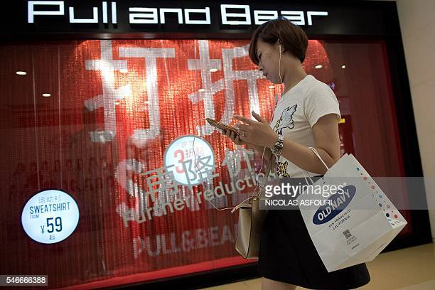 In this picture taken on July 12 a woman checks her phone while shopping at a mall in Beijing China's growth slipped to a new sevenyear low of 66...