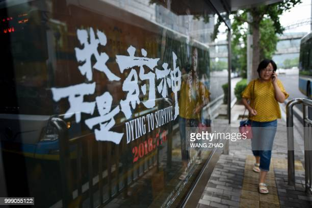 In this picture taken on July 12 a woman walks past a poster of the film 'Dying to Survive' at a bus stop in Beijing The screen portrayal of a cancer...