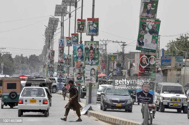 In this picture taken on July 16 Pakistani commuters drive along a road with posters of candidates taking part in the upcoming general elections in...