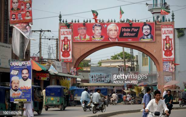 In this picture taken on July 17 Pakistani commuters drive past election posters displayed on a street in Peshawar Pakistan goes to the polls on July...