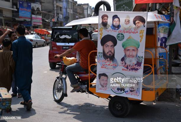 In this picture taken on July 2 Pakistani men walk past an election poster of a candidate from the Sunni Muslim religious party TehreekeLabbaik...