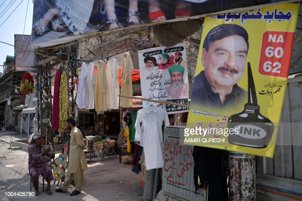 In this picture taken on July 2 Pakistani vendors wait for customers beside an election poster of candidate Sheikh Rasheed with the writing the...