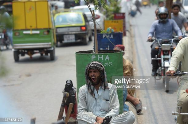 In this picture taken on July 22 a labourer yawns in the middle of a road as he waits for customers in Rawalpindi Nearly one year after the election...