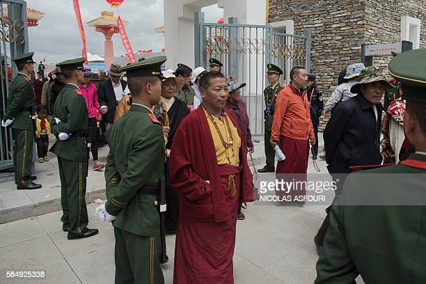 In this picture taken on July 25 Chinese paramilitary police secure an exit as Tibetans monks walk out from a stadium at the end of at a local...