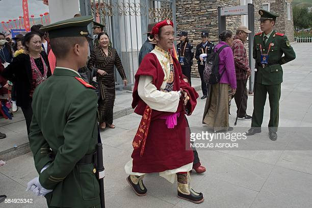 In this picture taken on July 25 Chinese paramilitary police secure an exit as an ethnic Tibetan in traditional dress walks out from a stadium at the...